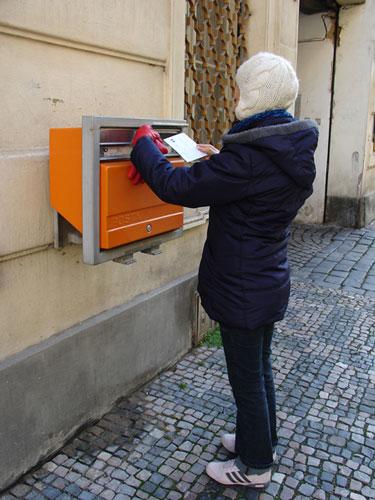 Foto de Sofía depositando postal en un buzón de Praga